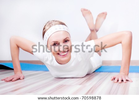 beautiful young blond woman working out on the mat at home