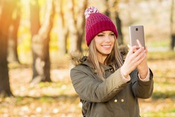 Beautiful young blonde Caucasian woman in olive green jacket and dark red knitted hat taking a selfie in autumn on smart phone. Medium retouch, vibrant colors, closeup, natural light.