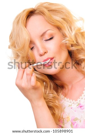 beautiful young blonde girl. closed her eyes. enjoys eating with a spoon. Close-up portrait on a white background