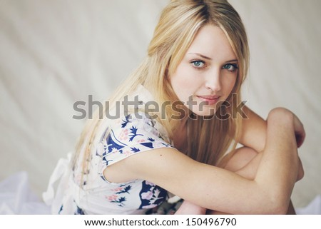 Beautiful young blonde girl dreamy-looking is sitting on the floor