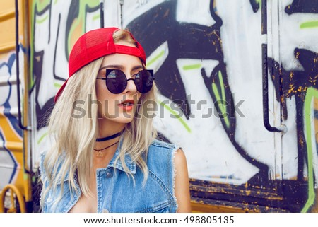 Beautiful young blonde girl dressed in a street style outfits posing in front of wagon full of graffitis. Wearing red cap, black sunglasses and choker around her neck with triangle.