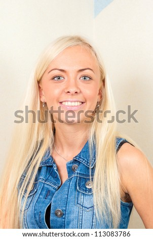 beautiful young blonde girl in a skirt and denim jacket smiling posing for photos