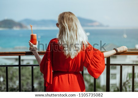 Beautiful young blonde girl in red dress and sunglasses drinking red cocktail from a glass on balcony. Against the background of the sea, mountains and sky. Back view.