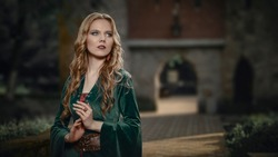 Beautiful young blonde girl in the medieval green dress keeps her hands together and looks away. The legends of Camelot and Lady Guinevere.