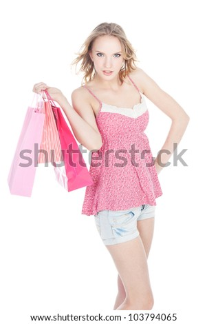 Beautiful young blonde girl with pink shopping bags over white