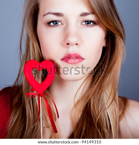 beautiful young blonde holding a red heart