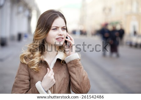 Beautiful young blonde in a fur jacket calling by phone #261542486