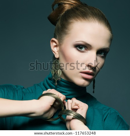 beautiful young blonde in green dress wearing wristbands over dark blue background. close up. studio shot