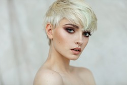 Beautiful young blonde model with short hair looking at camera