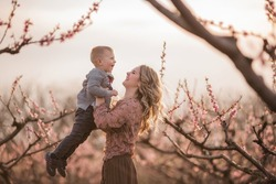 Beautiful young blonde mother with curly hair holding a little son in her arms in blooming gardens at sunset. Child care maternity concept. Mom throws the boy up, hugs, kisses, touches his forehead