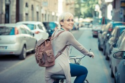 beautiful young blonde short hair hipster woman with bike in the city