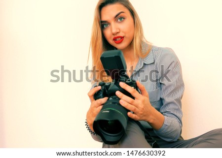 Beautiful young blonde with a big camera looks into the camera, toning #1476630392