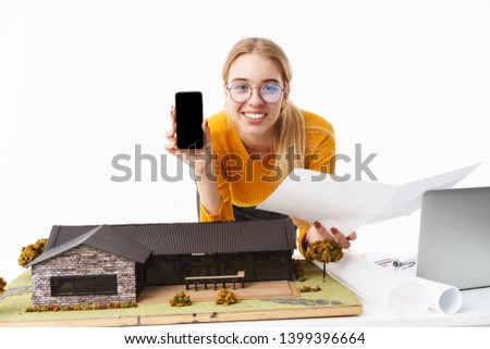 Beautiful young blonde woman architect standing isolated over white background, working on a new project at the desk with laptop, showing blank screen mobile phone #1399396664