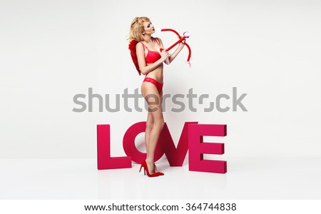 Stock Photo Beautiful young blonde woman as cupid angel with red wings and arrow, red lingerie. Studio photo on white background, standing next to love sign. Valentines day