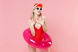 Beautiful young blonde woman girl in red one-piece swimsuit cap glasses with swim inflatable ring posing isolated on pink background. People summer vacation rest lifestyle concept. Put hands on chest