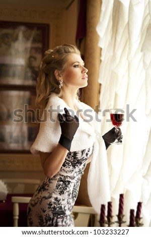 beautiful young blonde woman holding a glass of red wine in restaurant and waiting for her lover. Rich sexy girl in luxury dress black gloves and fur with healthy blond hair. Lady with diamond jewelry