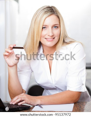 beautiful young blonde woman holding credit card