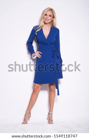 Beautiful young blonde woman in a nice fashionable blue dress. Christmas new year glamour photo.