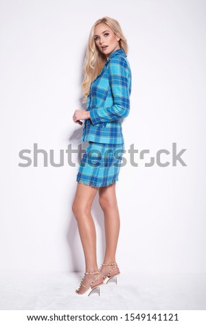 Beautiful young blonde woman in a nice fashionable blue suit, glamour photo.