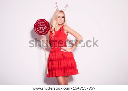 Beautiful young blonde woman in a nice fashionable red dress, holding a big stop sign. Christmas new year glamour photo.