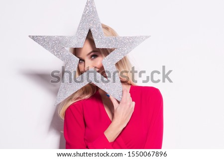 Beautiful young blonde woman in a sexy red dress, holding big glitter silver star. Christmas glamour photo. A lot of xmas gifts.