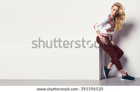 beautiful young blonde woman in a sweatshirt flower with pattern and jeans posing in studio. Fashion photo #391596520