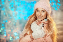 Beautiful young blonde woman in hat and mittens smiling outside on christmas background with lights.  Concept of holidays, christmas, new year, winter,  people.