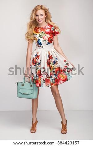beautiful young blonde woman in nice spring dress, handbag posing in a studio. Fashion spring summer photo