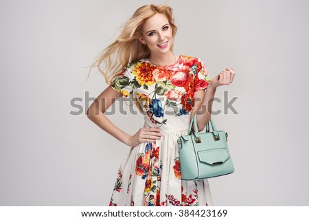 beautiful young blonde woman in nice spring dress, handbag posing in a studio. Fashion spring summer photo #384423169