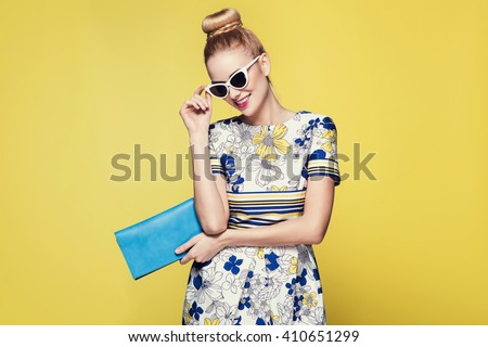beautiful young blonde woman in nice spring dress, posing on yellow background in studio. Fashion photo, blue handbag and white sunglasses