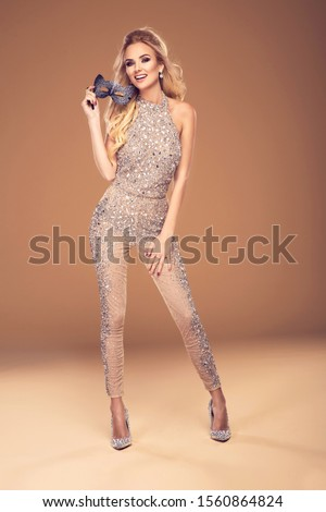 Beautiful young blonde woman in sexy glitter costume holding a mask. Party carnival glamour photo