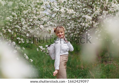 Beautiful young blonde woman in white shirt with backpack posing under apple tree in blossom and green grass in Spring garden