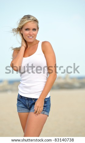 Beautiful young blonde woman in white tank top and denim shorts posing on a beach - holding her hair as it blows in the wind