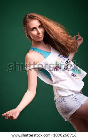 Beautiful young blonde woman in white top in denim shorts smiling and posing on a black isolated background