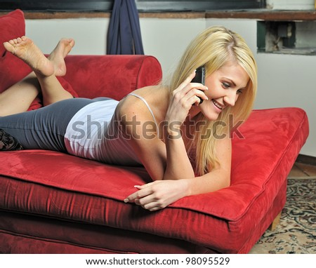Beautiful young blonde woman lounging on red chaise lounge (chaise longue) chair in white tank top and and gray athletic pants smiling as she talks on cell phone - looking down