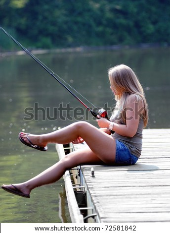 Beautiful young blonde woman scratches her leg while fishing from a pier