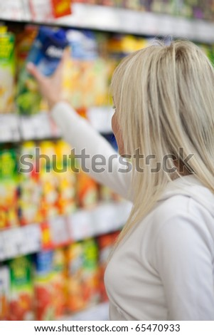 Beautiful young blonde woman shopping for fruit juices/soft-drinks/beverages in a grocery store/supermarket (shallow DOF; color toned image)