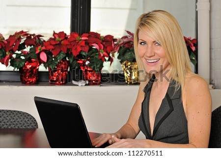 Beautiful young blonde woman sitting in office working on computer at desk - smiling