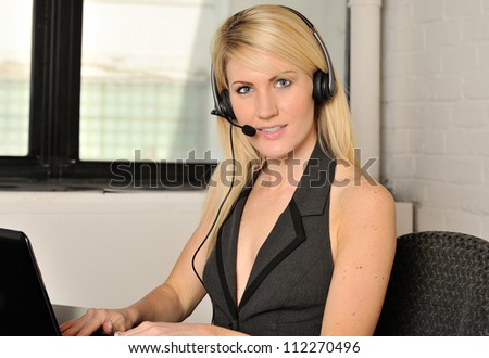 Beautiful young blonde woman sitting in office working on computer at desk while wearing telephone headset - stock photo
