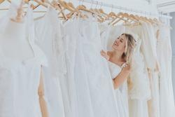 Beautiful young blonde woman standing Choosing a wedding dress.
