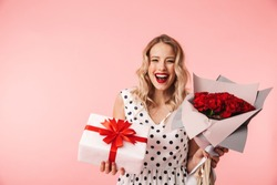 Beautiful young blonde woman wearing dress standing isolated over pink background, holding bouquet of roses and a gift box