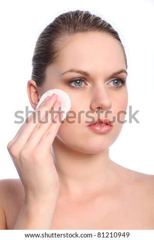 Beautiful young blonde woman with bright blue eyes using cosmetics cotton pad to apply make up to face.