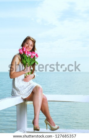 Beautiful young blonde woman with pink tulips blue sea and sky