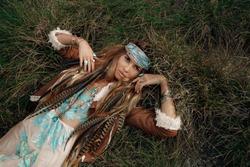 beautiful young boho girl in jacket lying down on grass