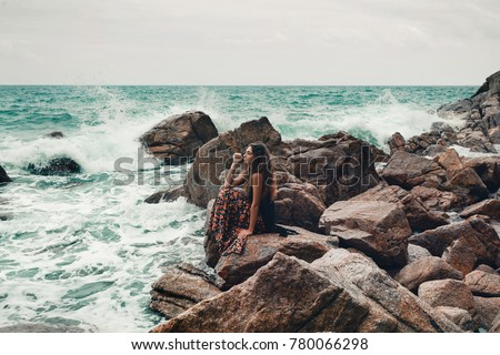 Beautiful young boho styled woman sitting on a stone beach #780066298