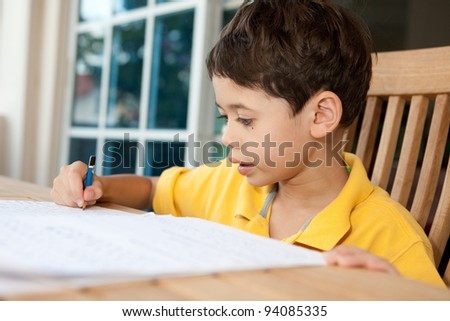 Beautiful young boy doing his homework at home