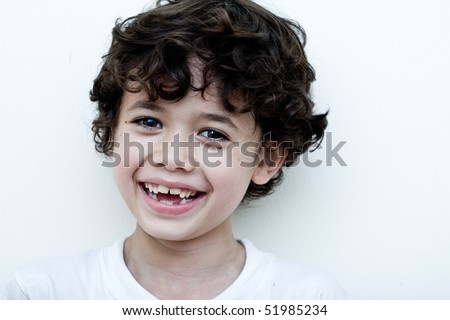 Beautiful young boy laughs as he shows his two missing teeth