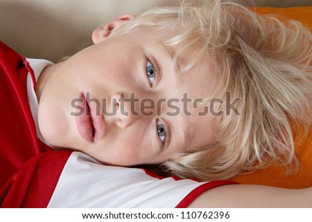 Beautiful young boy laying down on a sofa at home and wearing a red and white football shirt.