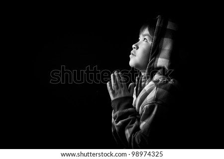 Beautiful young boy praying on black background in black and white