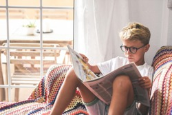 Beautiful young boy reading a newspaper at home. Blonde child reads news on a journal. Generation z child looking last-minute news on a paper magazine. information interest culture educational concept